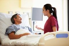 Paciente de Talking To Male de la enfermera en sitio de hospital fotos de archivo