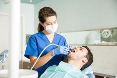 Paciente de Treating Mid Adult do dentista na clínica dental fotografia de stock
