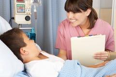 Paciente de visita da criança da enfermeira na divisão Fotos de Stock
