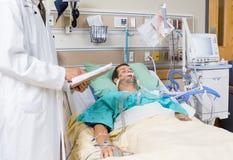 Paciente del doctor With Clipboard Examining médico Foto de archivo libre de regalías