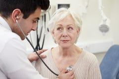 Paciente del doctor Examining Senior Female en hospital imágenes de archivo libres de regalías
