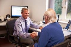Paciente del doctor Greeting Senior Male con el apretón de manos Fotos de archivo