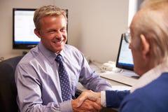 Paciente del doctor Greeting Senior Male con el apretón de manos Fotos de archivo libres de regalías