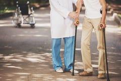 Paciente del doctor Helping Old Man con las muletas imagen de archivo