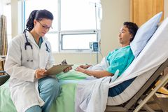 Paciente del doctor Holding Clipboard While que mira fotos de archivo libres de regalías