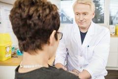 Paciente del doctor Looking At Female antes de la donación de sangre foto de archivo libre de regalías
