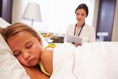 Paciente del doctor Observing Sleeping Child en cama de hospital Imagen de archivo libre de regalías