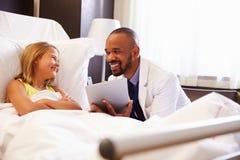 Paciente del doctor Talking To Child en cama de hospital fotos de archivo