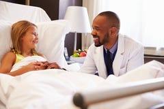 Paciente del doctor Talking To Child en cama de hospital Foto de archivo