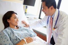Paciente del doctor Talking To Female en sala Imagen de archivo libre de regalías