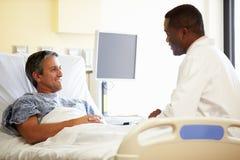 Paciente del doctor Talking To Male en sitio de hospital Foto de archivo