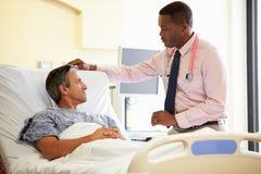 Paciente del doctor Talking To Male en sitio de hospital Imágenes de archivo libres de regalías