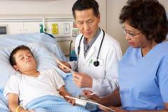 Paciente del niño del doctor que visita y de la enfermera en sala Fotografía de archivo libre de regalías