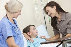 Paciente del niño del muchacho en madre y doctor de la cama de hospital fotografía de archivo