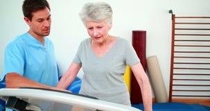A paciente del terapeuta físico mostrando cómo utilizar la máquina del ejercicio Imagenes de archivo