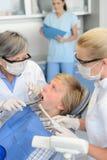 Paciente dental del adolescente del tratamiento de la enfermera del dentista Fotos de archivo libres de regalías