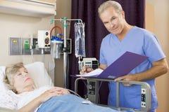 Paciente do doutor Making Nota Sobre Seu Imagens de Stock