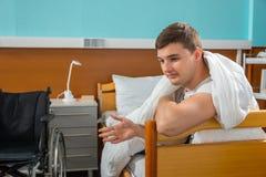 Paciente doente masculino que inclina-se na armação da cama do hospital coberta com o q foto de stock