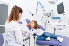 Paciente e dentista pequenos no armário Fotos de Stock