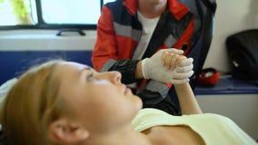 Paciente en ambulancia que pide que el paramédico dé la ayuda moral, llevando a cabo la mano del doc. almacen de video