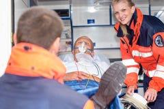 Paciente en coche de la ambulancia con rescate de los paramédicos Imagen de archivo libre de regalías