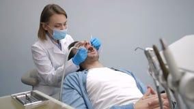 Paciente en la silla dental que consigue el tratamiento de los dientes almacen de video