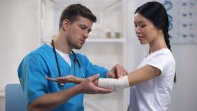 Paciente fêmea da urdidura elástica atenta do cotovelo da fixação do terapeuta após a saúde de ferimento vídeos de arquivo
