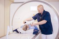 Paciente fêmea de Putting Headphones On do radiologista que submete-se a MRI imagens de stock