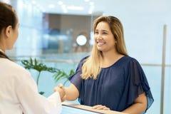 Paciente fêmea de sorriso que agita a mão no doutor imagem de stock
