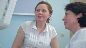 Paciente fêmea de sorriso que fala a um doutor na frente do dispositivo do ultrassom Fotografia de Stock Royalty Free
