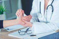 Paciente fêmea no exame médico do doutor ortopédico para o injur do pulso fotos de stock