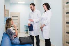 Paciente fêmea que está sendo tranquilizado pelo doutor In Hospital Room imagem de stock royalty free