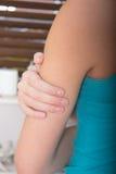 Paciente fêmea que guarda seu braço Imagens de Stock Royalty Free