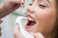 Paciente fêmea tratado com o equipamento dental para a cor exata do dente da determinação imagem de stock