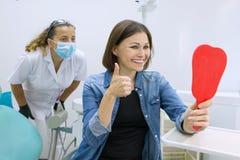 Paciente feliz de la mujer que mira en el espejo los dientes, sentándose en la silla dental foto de archivo