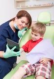 Paciente feliz del niño en el dentista que usa la tableta inalámbrica Foto de archivo