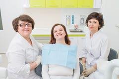 Paciente feliz en una oficina del dentista con el doctor y el ayudante que miran la cámara y la sonrisa fotos de archivo