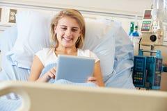 Paciente femenino adolescente que se relaja en cama de hospital Fotos de archivo