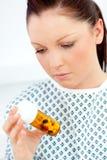 Paciente femenino caucásico que mira píldoras Imagen de archivo libre de regalías