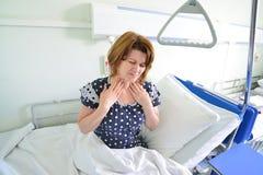 Paciente femenino con angina en cama en sala de hospital foto de archivo libre de regalías