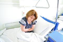 Paciente femenino con dolor abdominal en cama en sala de hospital Fotos de archivo libres de regalías
