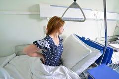 Paciente femenino con dolor de espalda en cama en sala de hospital Imágenes de archivo libres de regalías