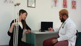 Paciente femenino con las muletas que discute su condición con el doctor que hace notas metrajes