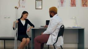 Paciente femenino con las muletas que discute su condición con el doctor que toma notas almacen de video