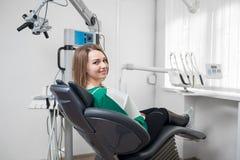 Paciente femenino con los apoyos en los dientes que se sientan en silla dental y que sonríen después del tratamiento en la clínic fotos de archivo