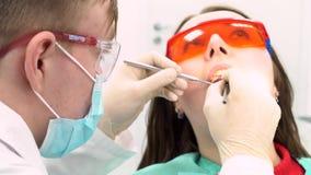 Paciente femenino con un doctor que intenta examinarla en una oficina del dentista, concepto del cuidado dental media Una chica j almacen de video