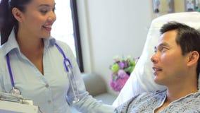 Paciente femenino de Talks To Male del consultor en sitio de hospital almacen de metraje de vídeo