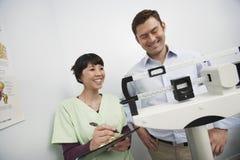 Paciente femenino del doctor Checking Weight Of fotos de archivo libres de regalías