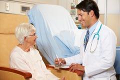 Paciente femenino del doctor Taking Notes From Senior asentado en silla Imágenes de archivo libres de regalías
