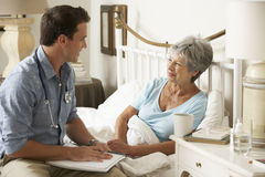 Paciente femenino del doctor Talking With Senior en cama en casa imágenes de archivo libres de regalías